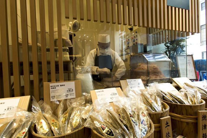 """ここ日本橋本店は、いわば""""鰹節出汁""""のテーマランド。  店内には、「にんべん」が選び抜いた逸品、開発した様々な商品が並べられる他、プロによる実演販売、""""出汁""""が味わえるスタンディングバーが設けられ、本物の鰹節の風味や美味しさ、伝統食品の素晴らしさを楽しむことが出来ます 【「にんべん日本橋本店」店内では、プロの削り師による本枯鰹節の削り実演行われ、削りたての鰹節が購入できる。】"""
