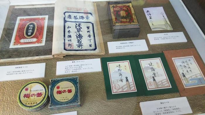"""日本橋は、江戸前の魚介や諸国の逸品が荷揚げされ、それらが取引されることによって、繁栄した街です。 """"商う""""ことを通じて、人も文化も、街も育まれ、その軌跡は止まることなく今も続いています。界隈には、江戸の粋と技が冴えた雑貨や食物、和菓子の老舗も数々残り、今も暖簾を掲げてその伝統技を守り続けています。 【明治初期の海苔缶やラベル等、貴重な資料が並ぶ「山本海苔店」店内展示ケース】"""