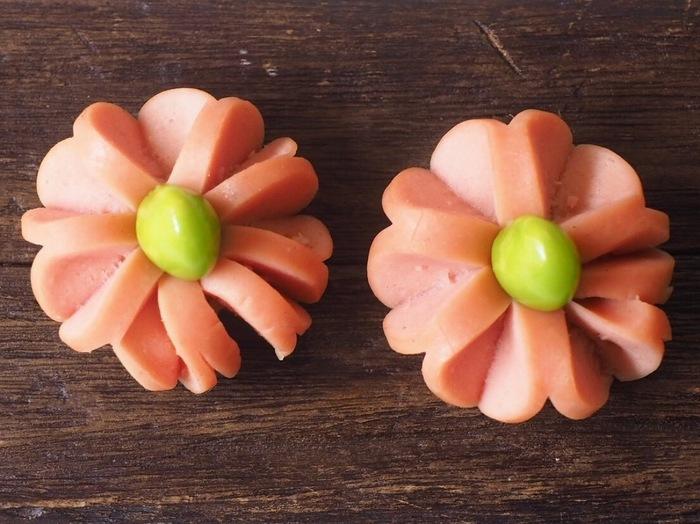 こちらはウィンナーの花びらの中心に枝豆を組み合わせたタイプ。パスタがないときには、つまようじでも留められますよ。ウィンナーの切込みを90度ずらして2回に分けて入れるのがコツです♪