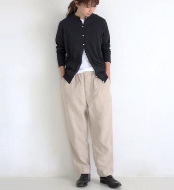 ベージュのテーパードパンツに、白トップスと黒のカーディガンを合わせたコーディネート。ベーシックなアイテムを合わせた着こなしには、ヘアアレンジやアクセサリーで女性らしさをプラスするのもおすすめです。