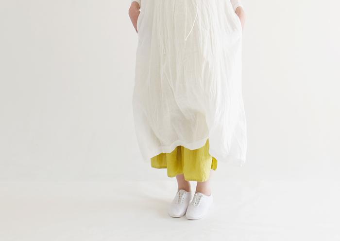 モノトーンコーデとは逆に、可憐な白いワンピースの裾からチラリとミモザカラーを覗かせて。こんな見せ方なんだか新鮮ですよね。春の重ね着オススメコーデです。