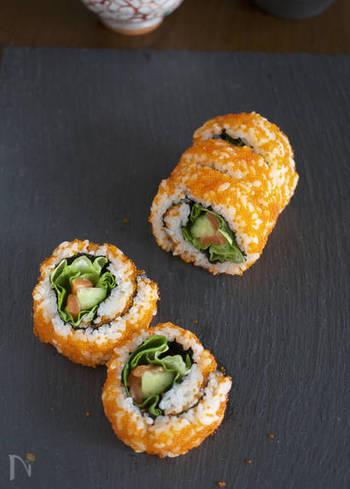 巻き簾→海苔→ご飯→とびっこと乗せた後にクッキングシートを重ねてそのまま裏返しにし具材を置いて巻いていく、基本の裏巻き寿司のアレンジバージョン。巻き簾の代わりにラップでもOKです。彩りもよくワクワクするレシピですね。