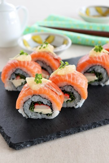 裏巻き寿司を作っておき、さらにラップにサーモンを並べ作っておいた裏巻き寿司を乗せて形を整えて作る「サーモンとクリームチーズのロール寿司」。具材を変えればアレンジ色々楽しめますよ。楽しんで作ってみてくださいね。