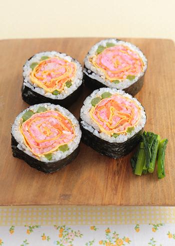 サーモン、カニカマ、薄焼き卵を組み合わせてバラの花びらに見立てた「お花の太巻き寿司」。食べるのがもったいない気持ちになってしまう可愛い太巻きです。