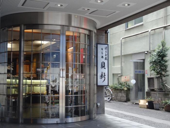 """「日本橋 貝新」は、慶長年間に創業した伊勢桑名発祥の佃煮店。 日本橋に店を構えてから130年の歴史を誇る老舗の佃煮店です。三重桑名から暖簾分けした店名通り「貝新」は、蛤やあさりといった""""貝""""の佃煮が絶品のお店です。  店内には、アサリやシジミ、小柱といった貝類の佃煮が並ぶ他、昆布やしいたけ、葉唐辛子やきゃら蕗といった定番の佃煮も各種揃っています。"""