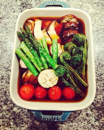揚げずにヘルシーな焼き浸しもおすすめ。グリルで焼いた野菜やこごみが熱いうちに、だしに浸します。味がよくなじんでから、いただきましょう。彩りもきれいですね。