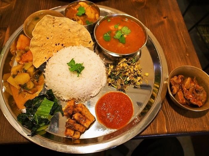 絶品のカレー屋さんが集う谷町エリアで、ヒマラヤの麓・ネパールのワンプレートカレー『ダルバート』を提供するのが「ダルバート食堂」です。シルバーのプレートが本場の雰囲気たっぷり。この上で、ごはんとおかずを混ぜていただきます。