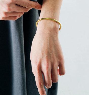 真鍮素材のシンプルなゴールドバングルは、ハンドメイドにこだわって作られたアイテム。アンティークのような繊細さを感じさせるアクセサリーで、華奢なデザインがナチュラルコーデに馴染みます。