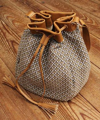 小紋柄をジャガード生地であしらった、オリエンタルな雰囲気のある巾着バッグ。タッセル付きのストラップが、トレンド感をしっかりアピールしてくれます。