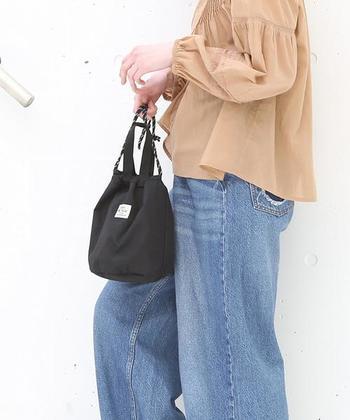 ミニサイズの巾着バッグは、最低限の荷物を持ち歩きたい人にぴったりなアイテム。スポーティーな印象のナイロン素材は、リバーシブルでデザインを変えて使うこともできます。