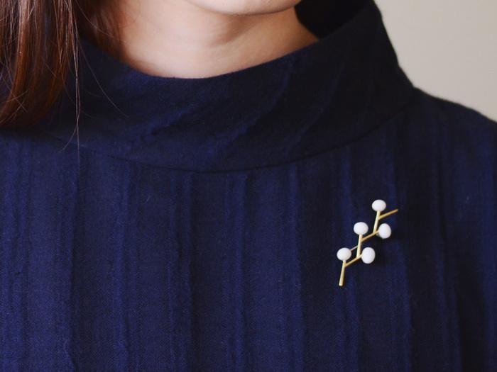 フタリシズカという花をモチーフにして作られたブローチ。白とゴールドのシンプルな組み合わせが、上品な雰囲気を演出してくれます。テイストを選ばないので、何だか物足りないと感じた日に気軽に身に着けられるのが魅力です。