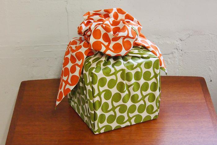 こちらの風呂敷は、三巾(みはば)と呼ばれる104×104cmの大きさ。テーブルクロスやエプロンとしても重宝するサイズです。一面がグリーン、もう一面がオレンジになっています。贈り物のラッピングをするときに、面の色が違うことを生かした包み方をするのも楽しそうですね。