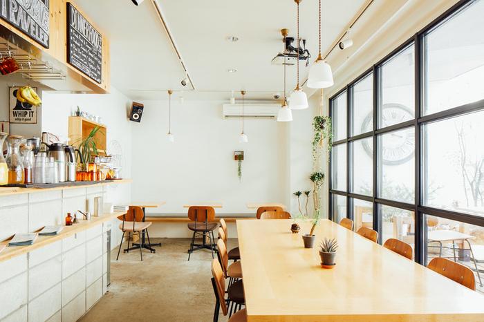 1階のカフェは、温かい木の温もりが感じられる白を貴重とした、爽やかな空間です。ところどころに設えられた植物も柔らかな雰囲気を演出します。  朝7時から営業しており、東京のガイドブックや地図も置いてあるので、散策の作戦会議に利用するのにぴったりです。