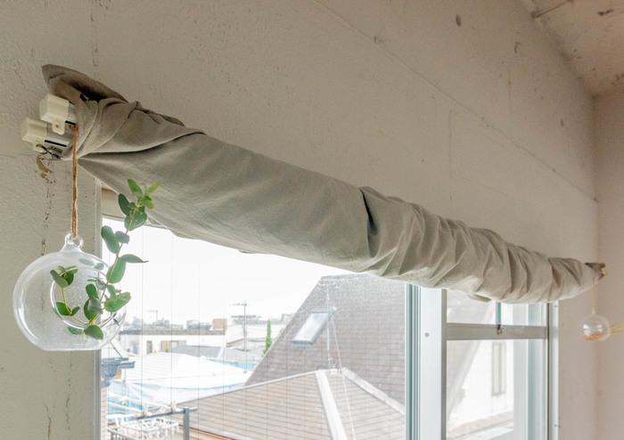 カーテンの代わりに大きな布をくるくると巻きつけて、雰囲気のある個性的な窓辺に。 ガラスのフラワーベースを吊るせば、爽やかな窓辺になります◎