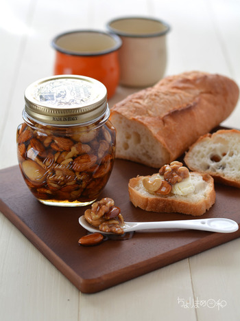 アーモンドやくるみなどのナッツ類をはちみつで漬けた瓶漬けも、幅広く使えるお役立ちレシピ。  好みのナッツをオーブンで焼き、はちみつと瓶漬けするだけの簡単レシピ。パンにのせたり、酢やオイルを加えてマリネにしたりして活用できます。  常温で冷暗所に保存すれば、約1年ほど日持ちするのも◎。