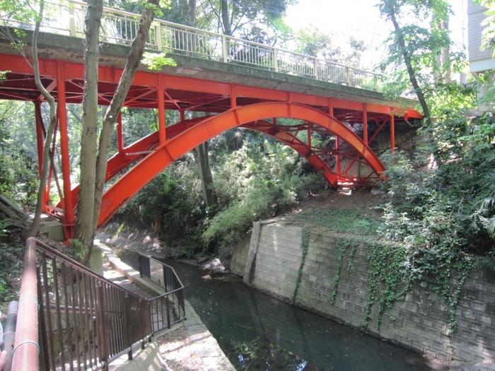 東急大井町線・等々力駅からアクセスする場合には、赤い「ゴルフ橋」がある渓谷入口がスタート地点になります。かつてこの辺りに広大なゴルフ場があったことから「ゴルフ橋」と名付けられたそうです。渓谷入口の階段を降りてすぐに見えるゴルフ橋は、等々力渓谷の見どころのひとつとして知られています。
