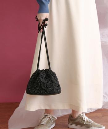 パールをたっぷりとあしらって、とってもキュートに仕上げたミニサイズの巾着バッグです。黒を選べば甘くなり過ぎず、シンプルながらも大人可愛いバッグ使いが楽しめます。