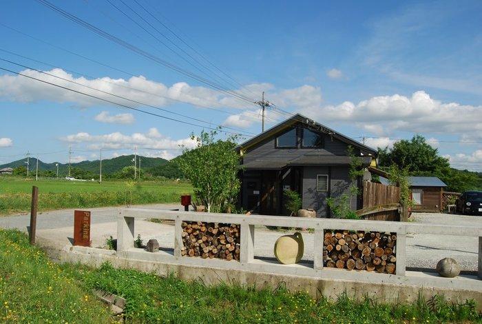 田んぼの中にポツンと建つセンスのいいログハウス風の一軒家。青々と生い茂る草木や山が美しく、心も体も解放されるような心地いい場所です。  駐車場にある薪は、秋冬につかう薪ストーブ用のもの。なんとマスターの勝田さんが、山から切って用意したものなんです! 「ボタンひとつで簡単にできる時代、あえて無駄や手間のかかることが楽しい」と、薪割りもしんどくならない適度に楽しんでいるそうですよ。
