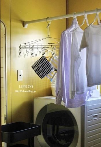 ランドリールームの壁に突っ張り棒を設置し、室内干し用スペースを確保。洗濯機の近くに配置することで、取り出してすぐに干せるメリットがあります。