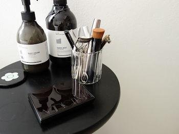 小さなガラスカップなどにメイク道具を立てて収納。化粧品の美しいデザインを生かした見せる収納です。
