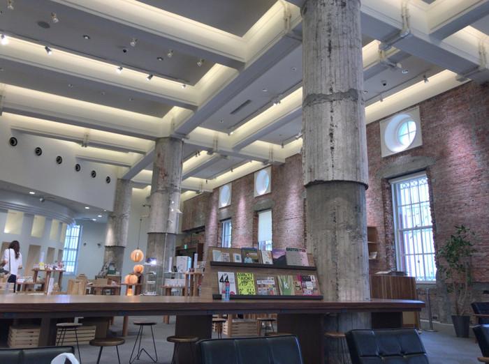 天井が高く開放感のある店内。カフェの隣はOita Madeブランドの商品が並ぶ「Oita Made Shop」になっています。修復再現されたコンクリートの柱や化粧梁に歴史を感じますね。