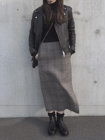 トラッドなグレンチェックのタイトスカートに、ライダースジャケットを合わせたシャープな着こなし。サイドに大きめに入れられたスリットが、立体的なシルエットに。