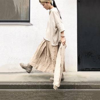 生成りカラーのチェックのロングスカートには同じく生成りの柔らか素材のトップスをチョイス。ルーズなバランスで着こなすと◎