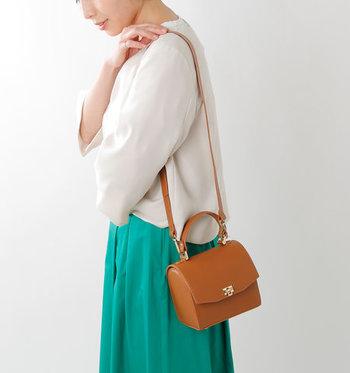 コンパクトなサイズ感のハンドバッグは、ストラップを付けてミニショルダーとしての活用もOK。小ぶりなのでドレスアップスタイルに合わせてもこなれた印象に◎