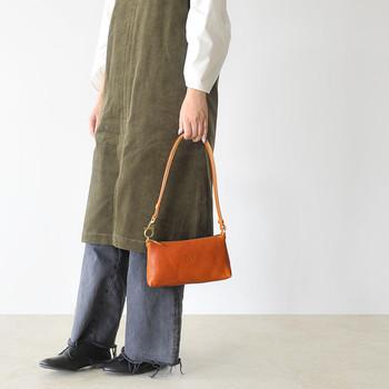 牛革で作られた、光沢感のあるアクセサリーポーチです。長めのストラップが付いているので、ポーチと言ってもバッグ感覚で使えるのが魅力的。付属のナスカンで、メインバッグの持ち手に付ける使い方もできます。