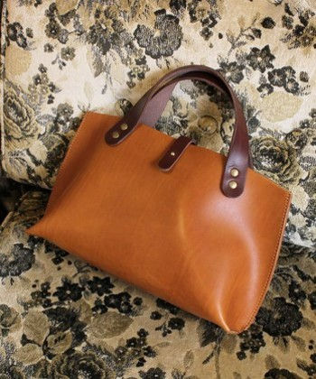 コンパクトなサイズ感のハンドバッグは、牛革で作られたリッチ感のあるアイテム。トーン違いのブラウンを2色組み合わせていて、持っているだけでおしゃれ度がグッとアップしそうですよね♪