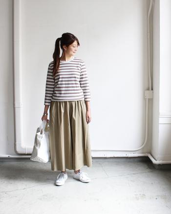 ベージュ系のカフェカラーボーダートップスに、同系色のロングスカートを合わせたコーディネートです。七分袖トップスで全体に軽い印象を与えつつ、白小物で爽やかにまとめています。