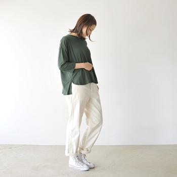 深緑の七分袖トップスに、白パンツとスニーカーを合わせたカジュアルなコーディネートです。緑が暗めな分、白アイテムで明るさをしっかり演出。大人のカジュアルコーデの完成です。