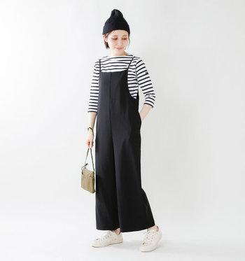 白黒のシンプルな七分袖ボーダートップスに、黒のサロペットを合わせたコーディネートです。黒で合わせたニット帽と、ベージュ系の小物でとことんシンプルな着こなしに。