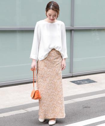 七分袖とさりげないスリットデザインが、シンプルな白トップスをこなれ感たっぷりに見せてくれるコーディネート。タイトな柄スカートとバッグはオレンジをチョイスして、女性らしい春の装いが素敵ですね。