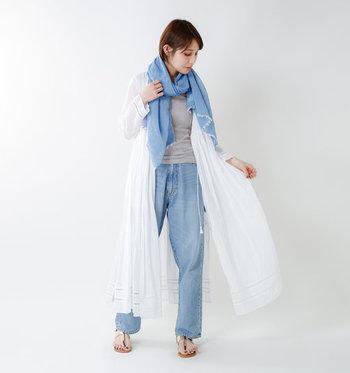 グレーのトップス×デニムパンツのシンプルコーデに、白のワンピースをガウン風に羽織ったスタイリングです。首元に青のストールを一枚プラスすると、それだけで爽やかさがグッと上がりますね。