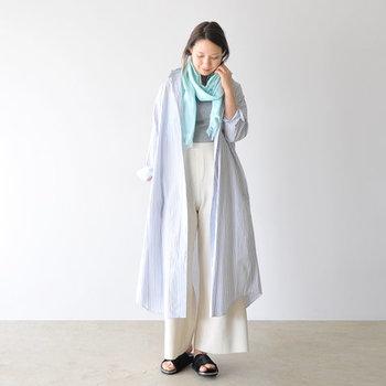 グレーのTシャツに白のワイドパンツを合せた、シンプルラフなコーディネート。ストライプのシャツワンピースをさっと羽織って、水色のストールを首元にぐるりと巻いています。ラフなのにお出かけもOKの、大人の休日スタイルの完成です。
