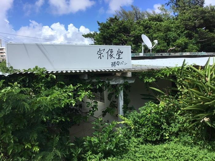 宜野湾の「宗像堂(ムナカタドウ)」は、日本各地の催事などでもファンが多い人気店。外人住宅街を進んでいくと、ふっと緑に囲まれたお店が現れます。
