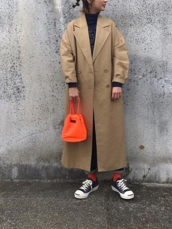 靴下とバッグ、ふたつの小物を同じ色にすることで、着こなしに統一感が。鮮やかなオレンジは派手になりすぎず、カジュアルな印象に。