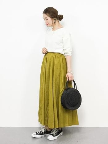 こちらは鮮やかなイエローのスカートをポイントにした、女性らしい雰囲気のカジュアルスタイルです。華やかで可愛らしい印象のカラースカートも、ブラックのかごバッグで大人っぽい雰囲気に。