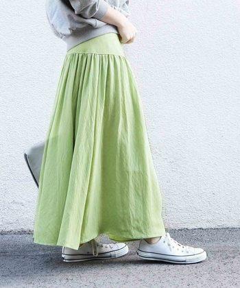 爽やかなグリーンのロングスカートには、スウェットとスニーカーを合わせて軽快に着こなしたい。
