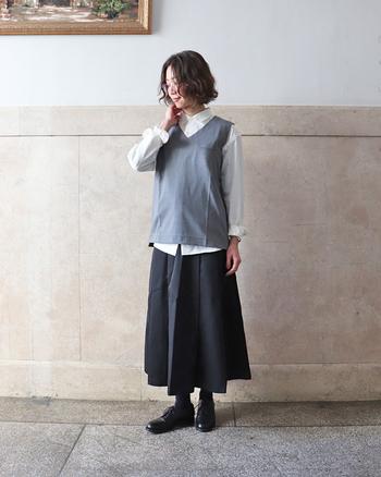 ベーシックな白シャツに、グレーのVネックベストを重ねたコーディネート。黒スカート靴下とシューズも黒で合わせて、クールなのにどこか女性らしい、上品スタイルの完成です。