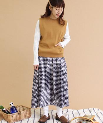 濃いベージュカラーのニットベストは、白のリブトップスとギンガムチェック柄のロングスカートに合わせて。白の靴下や茶色のローファーシューズが、ナチュラル感をグッとアップしてくれます。
