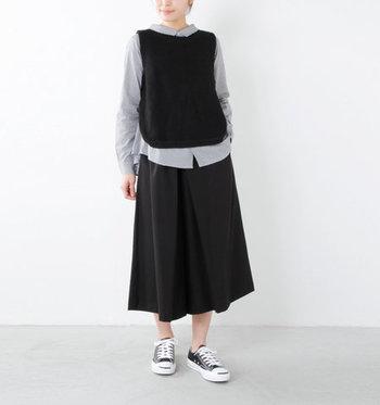 黒のニットベストを、シャツの上にレイヤードした上品なコーディネートです。ボトムスは黒のスカートでセットアップ風に着こなして、足元をスニーカーにすることでカジュアル感をプラス。