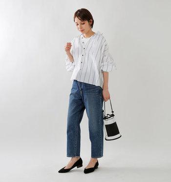 ストライプデザインの白シャツに、デニムパンツを合わせたベーシックなコーディネートです。足元には黒のパンプスをチョイスして、シンプルな中にも洗練された印象を与えるスタイリングに仕上げています。