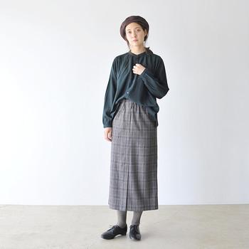 深緑のトップスに、グレーのチェック柄タイトスカートを合わせたマニッシュなコーディネート。グレーのタイツに黒のレザーレースアップシューズを合わせて、大人っぽさをアピールしています。