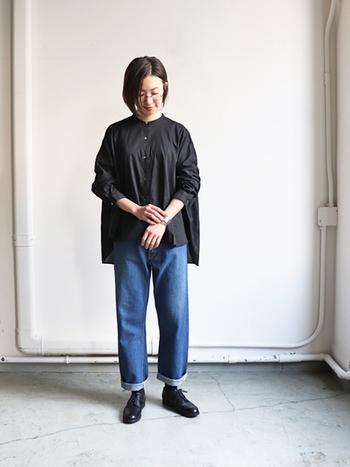黒のゆったりシャツに、シンプルなデニムパンツを合わせたコーディネートです。足元はトップスと揃えた黒シューズで、ちょっぴりメンズライクな着こなしに。