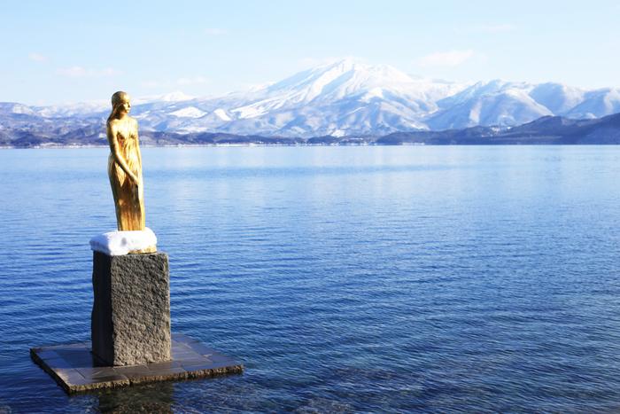 田沢湖は、日本一深い湖として知られています。水深は423.4mで周囲の山々の雪や緑を映す美しい名所として、多くの人々に親しまれています。湖面にたたずむブロンズ像は「たつこ像」。永遠の若さと美貌を願い、龍の姿の湖神となったという「たつこ姫伝説」に由来していて、静かな表情を見せています。