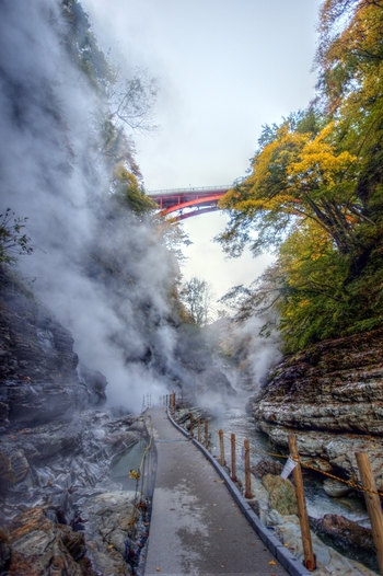 橋から約200段の階段を降りると、その先には遊歩道が続いています。あちこちで熱湯と蒸気が激しく噴出する大噴湯の迫力に驚かされます。赤い橋と紅葉、白煙のコントラストは、ここでしか見られない絶景です。