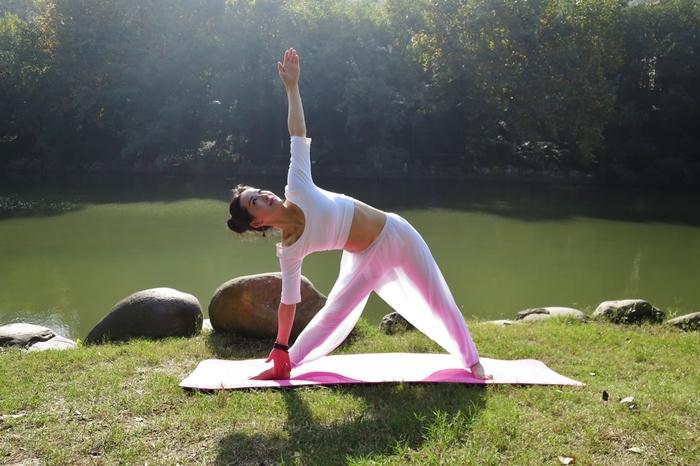 初心者でもできる三角のポーズ。両足を大きく開いて、右のつま先は90度右側へ、左のつま先は前を向くように立つのがポイント。腰痛や便秘に効果的で、ウエストやヒップを引き締めるという、美容に嬉しいポーズです。