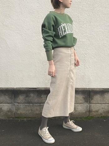 ベージュのスカートに、くすんだ色味のスウエットをチョイス。タイツもグレーにして、全身をスモーキーな色合いにするのが洒落て見えるコツですね。